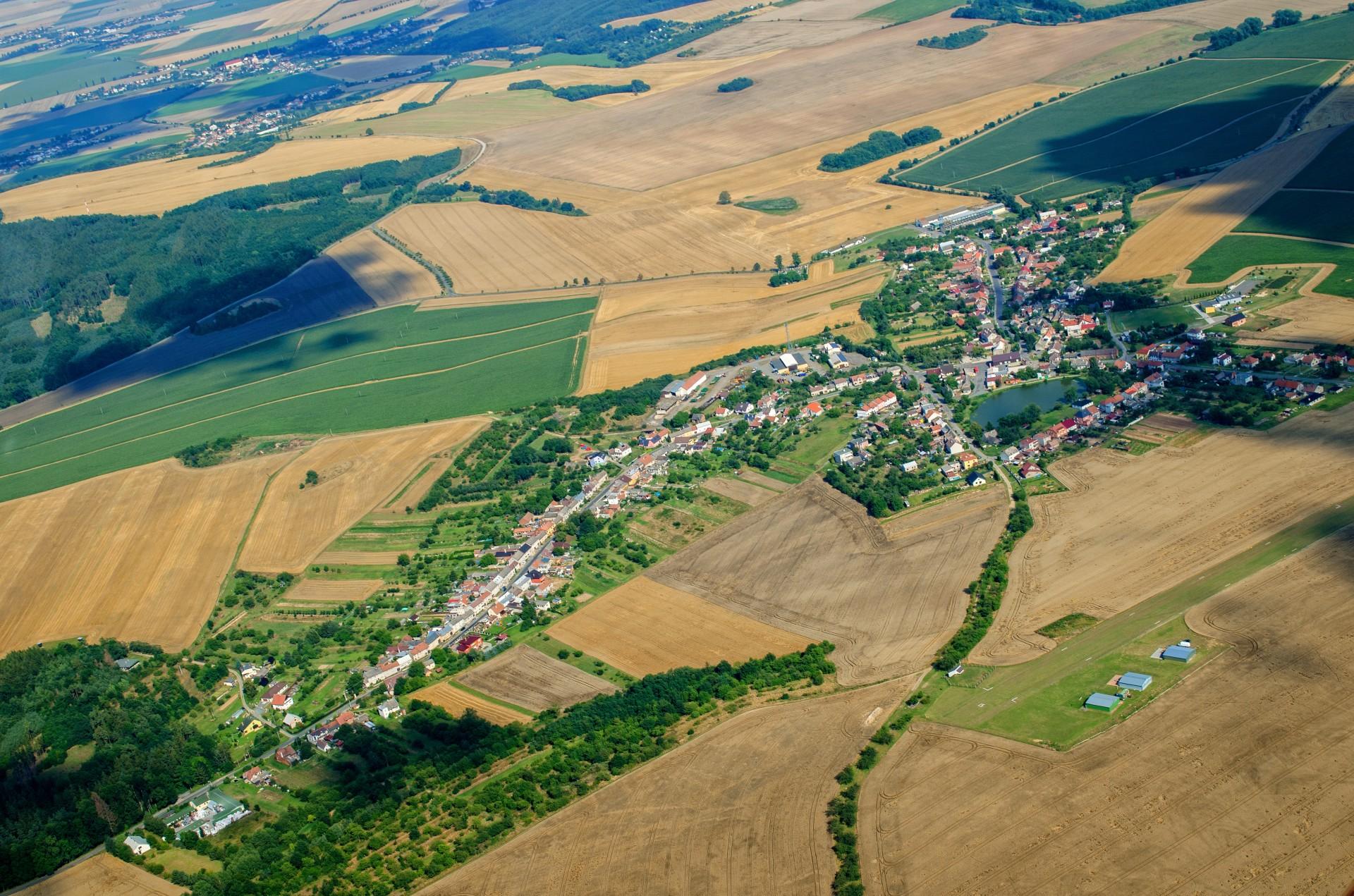 Luftbild mit Dorf und Ackerflächen